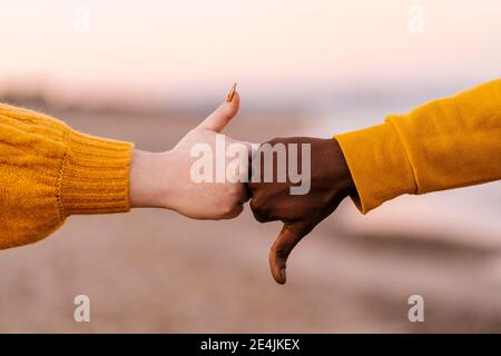 Man and woman gesturing with thumps up and down at beach
