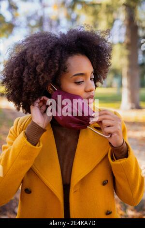 Young woman removing protective face mask while standing at park - Stock Photo