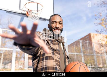 Happy young man gesturing while holding basketball in court on sunny day