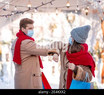 Man and woman in protective masks greeting on street