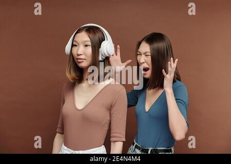 Young angry brunette woman shouting at her twin sister in headphones enjoying her favorite music while both standing in front of camera