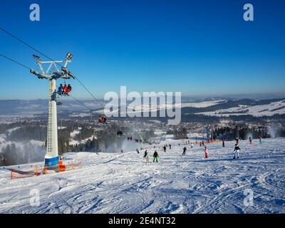 Ski slope, chairlift, skiers and snowboarders in Bialka Tatrzanska ski resort in Poland in winter. Snow cannons in action