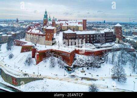 Krakow, Poland. Historic royal Wawel Castle and Cathedral in winter with white snow, walking people and promenade.