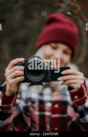 Portrait of young woman using camera in forest. Girl filming and smiling, lady in trendy shirt and red beanie hat.