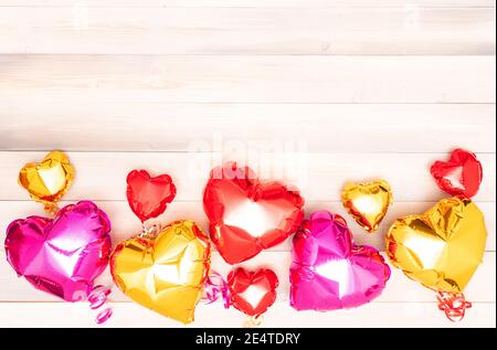 nine foil pink, red and golden balloons in the shape of a heart with ribbons on a white and beige wooden background. Valentine's Day. The 14th of February concept. banner with copyspace. place for text. flatlay - Stock Photo