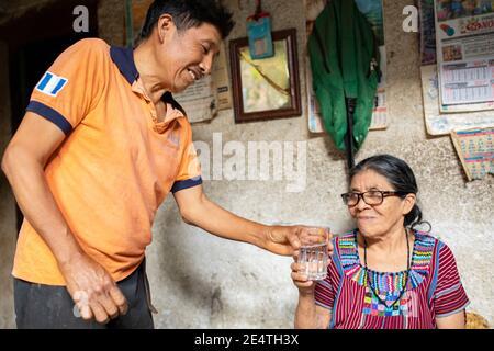 An elderly woman drinks a glass of clean water in San Juan la Laguna, Guatemala.
