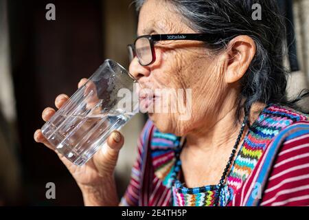 An elderly woman drinks a glass of clean water in San Juan la Laguna, Guatemala, Central America.