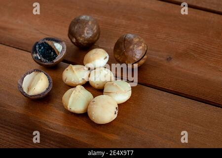Organic macadamia nuts on wooden table. Selective focus. Superfood and healthy food concept
