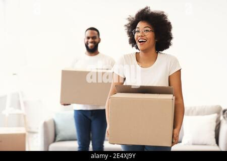 Excited African Couple Carrying Moving Boxes Entering Own Home