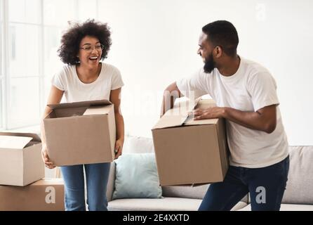 Happy African Couple Carrying Packed Moving Boxes Entering New Home