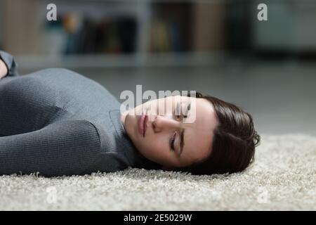Sad woman looking away lying on a carpet on the home floor