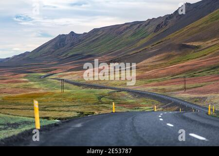 Icelandic landscape with a road snaking through a colorful sloping crested hill and a plain