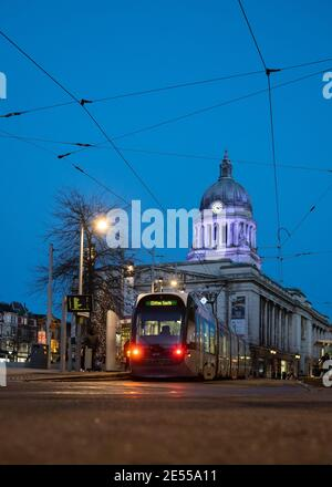Council house illuminated with tram parked in front lit up night street lamps cables train waiting passengers shoppers to board blue sky Nottingham