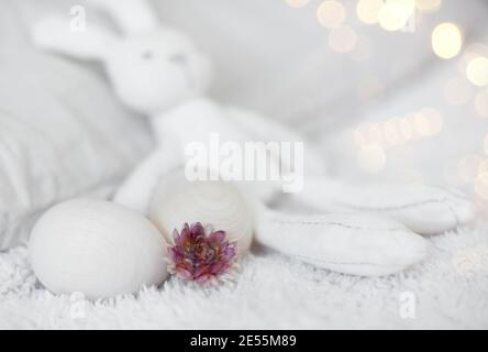 Easter funny white stuffed rabbit toy on a white bed with wooden eggs zero west. Stock Photo