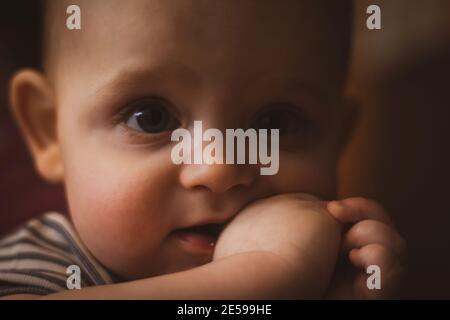 Teething in babies. Small caucasian boy is holding his fist in mouth. Selective focus. Close up photo. Dark toning.