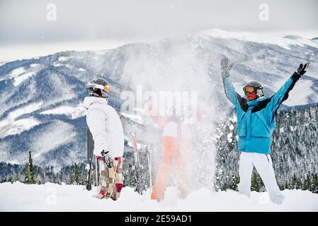 Friends skiers in ski suits throwing fresh powder snow high in the air. Two men and woman having fun on snowy hill with beautiful mountains on background. Concept of ski resort and friendship.