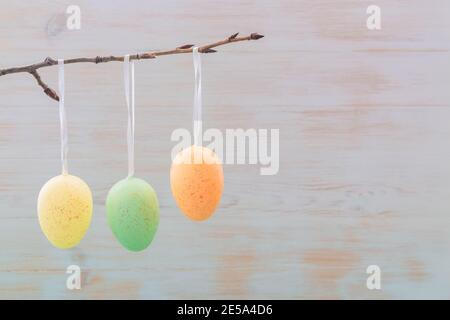 Easter eggs on branch in sping on wooden vintage background. Subtle gentle colored Eastern decoration. Easter mood. Minimalism. Copy space.