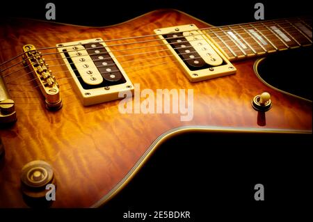 Close-up of vintage electric guitar with sunburst finish on a black background Stock Photo