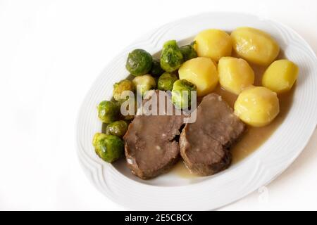 Slices of beef roast with boiled potatoes, brown sauce and fresh sprouts isolated on white background