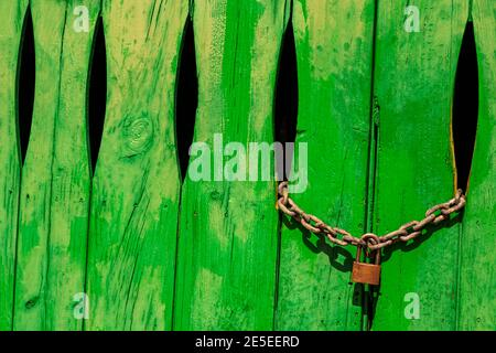 Green door in the stone wall with lock locked in Cala Figuera Mallorca Spain.