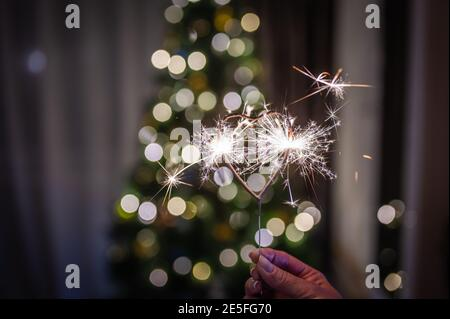 Bengal fire heart-shaped in the woman's hand burns against the background of a Christmas tree with colored garlands with bokeh
