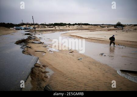 A man searches in a river stream following heavy rains and flooding on a beach of the Mediterranean sea near Kibbutz Nitzanim in southern Israel December 14, 2013. REUTERS/Amir Cohen (ISRAEL - Tags: ENVIRONMENT)