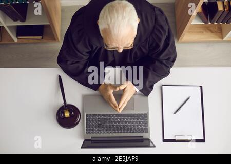 Trustworthy professional attorney or judge sitting at desk with laptop and gavel