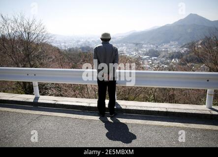 Fumiaki Kajiya, a 76-year-old atomic bomb survivor and retired school teacher, looks towards the city center from the street in front of his home in Hiroshima, western Japan, March 27, 2015. As the 70th anniversary of the world's first nuclear attack nears, many survivors still find it too painful to talk about. But with their ranks dwindling, others are determined to pass on their experiences to younger generations. A U.S. bomber dropped the atomic bomb on Hiroshima on August 6 1945, killing about 140,000 by the end of the year, out of the 350,000 who lived in the city. The city still has som