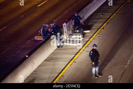 California Highway Patrol officers detain a person as they clear the 101 freeway from protesters in Los Angeles, California, following Monday's grand jury decision in the shooting of Michael Brown in Ferguson, Missouri, November 25, 2014.  U.S. President Barack Obama said on Tuesday anyone who destroys property in rioting against a Missouri grand jury's decision should be prosecuted, urging Americans upset by the court to work together to improve race relations.  REUTERS/Mario Anzuoni  (UNITED STATES - Tags: CRIME LAW POLITICS CIVIL UNREST)