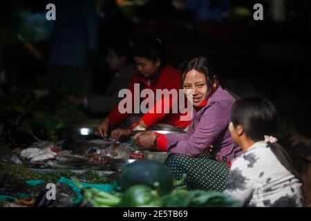 A woman chats with a fellow vendor as she sells fish at the Myitkyina market in the capital city of Kachin State, northern Myanmar February 23, 2012.  REUTERS/Soe Zeya Tun (MYANMAR - Tags: SOCIETY) Stock Photo