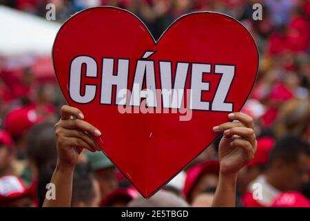 A supporter of Venezuelan President Hugo Chavez holds a sign during a rally at the People's Balcony at Miraflores Palace in Caracas April 13, 2012. Chavez commemorated ten years of his return to power after a brief coup that ousted him for two days in 2002. REUTERS/Carlos Garcia Rawlins (VENEZUELA - Tags: POLITICS ANNIVERSARY)