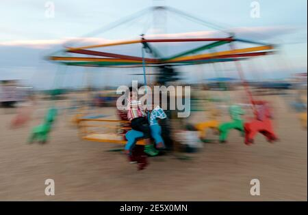 A boy rides on a merry-go-round on the Marina beach in the southern Indian city of Chennai August 31, 2012. REUTERS/Babu (INDIA - Tags: SOCIETY) - Stock Photo