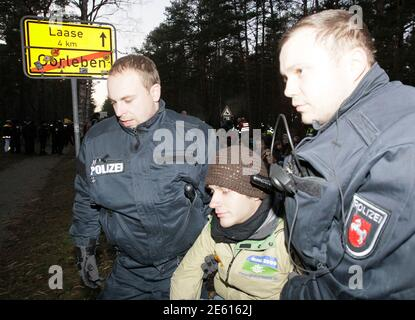 German police officers remove an anti-nuclear protester blocking a street to prevent the transportation of Castor nuclear waste containers (Cask for Storage and Transport of Radioactive material) in Gorleben November 28, 2011. The controversial shipment of 11 Castor containers with spent German nuclear fuel reprocessed in France, will be loaded onto trucks in Dannenberg before its final transportation to the nearby intermediate storage facility in the northern Germany village of Gorleben. REUTERS/Wolfgang Rattay (GERMANY - Stock Photo
