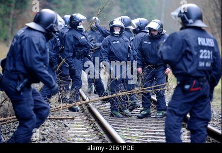 Police officers remove branches placed by anti-nuclear protestors from the railway tracks near Leitstade, November 25, 2011. The Castor (Cask for Storage and Transport Of Radioactive material) train is carrying 11 containers of spent German nuclear fuel on route from France after being reprocessed, to the nuclear waste storage facility of Gorleben in north eastern Germany this weekend. REUTERS/Fabian Bimmer (GERMANY)   - Tags: POLITICS CIVIL UNREST ENVIRONMENT) - Stock Photo