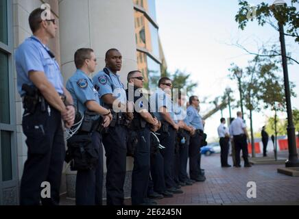 Police officers stand guard as demonstrators (not pictured) protest against the death of black teenager Michael Brown, outside St Louis County Circuit Clerk building in Clayton, Missouri August 12, 2014. Police said Brown, 18, was shot in a struggle with a gun in a police car but have not said why Brown was in the car. At least one shot was fired during the struggle and then the officer fired more shots before leaving the car, police said. But a witness to the shooting interviewed on local media has said that Brown had been putting his hands up to surrender when he was killed. The FBI has open