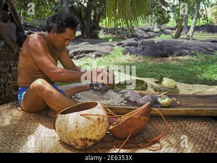 Man pounding taro root to make poi at the annual Establishment Day festival for Puuhonua O Honaunau National Historic Park, Island of Hawaii. - Stock Photo