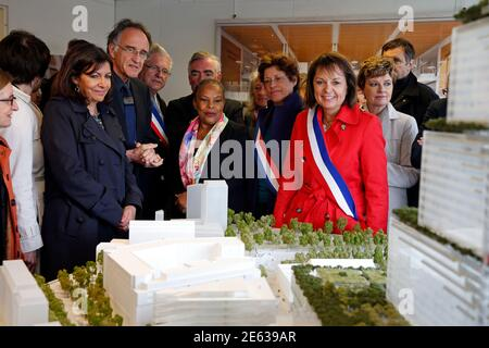 Paris mayor Anne Hidalgo (L), French Justice Minister Christiane Taubira (C), Bernard Plattner (2ndL), architect and Renzo Piano Building Workshop partner, Brigitte Kuster (R), mayor of the 17th district, look at the model of the new Law Court complex in Paris, France, May 6, 2015. The new Paris Courthouse, built on a former industrial zone, the ZAC Paris Clichy-Batignolles, scheduled to open in 2017, will house 90 courtrooms and will host more than 9,000 people daily. The courthouse, measuring 160 meters, will group all services of the Tribunal de Grande Instance of Paris and the police court - Stock Photo