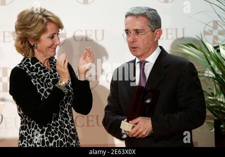 Former Colombian President Alvaro Uribe (R) is applauded by Madrid's regional president Esperanza Aguirre after receiving 'La puerta del recuerdo' award in Madrid October 27, 2010.   REUTERS/Juan Medina  (SPAIN - Tags: POLITICS)