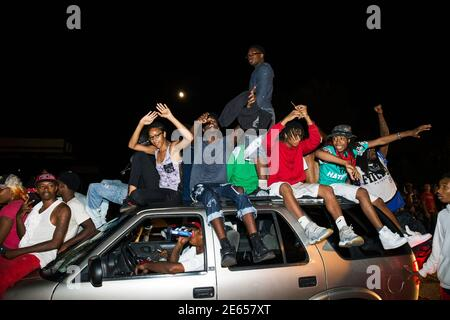 Protesters chant as they ride on a car during a peaceful demonstration as communities continue to react to the shooting of Michael Brown in Ferguson, Missouri August 15, 2014. Missouri's governor Jay Nixon moved to ease tensions on Thursday after days of racially charged protests over the police shooting of Brown, an unarmed black teenager, putting the African-American captain of the Highway Patrol Ron Johnson in charge of security in the St. Louis suburb of Ferguson. REUTERS/Lucas Jackson (UNITED STATES - Tags: CIVIL UNREST CRIME LAW) - Stock Photo