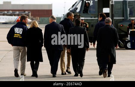 U.S. President Barack Obama (C) walks to Marine One upon his arrival in New York City to view recovery efforts from Hurricane Sandy, November 15, 2012. From L-R: Housing and Urban Development Secretary Shaun Donovan, Senator Kirsten Gillibrand, Senator Charles Schumer, Obama, Homeland Security Secretary Janet Napolitano, New York Governor Andrew Cuomo and New York Mayor Michael Bloomberg. Obama was due to visit areas of New York still without power on Thursday, 17 days after Superstorm Sandy tore across the eastern seaboard, showing his ongoing concern for victims of the storm even as his admi - Stock Photo