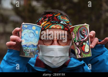 Beijing, Turkey. 27th Jan, 2021. Berk Armagan, a 26-year-old young man from Istanbul, shows his paintings on paper cups in Ankara, Turkey, Jan. 27, 2021. A Turkish self-taught artist and traveller draws the sites around the world that he visits on simple paper coffee cups he uses as canvas to fund his globetrotting passion. Credit: Mustafa Kaya/Xinhua/Alamy Live News