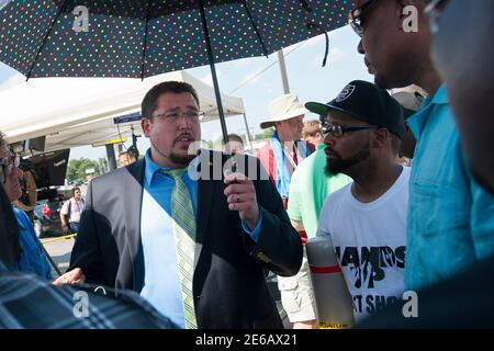 Ferguson Mayor James Knowles III engaged in a brief dialogue with opposition leaders in Ferguson, Missouri on August 19, 2014. Some, like Malik Shabazz (R), national president of Black Lawyers for Justice, said that while he may not agree with the policy decisions of Mayor Knowles, he stated that a dialogue was necessary to move forward. REUTERS/Mark Kauzlarich (UNITED STATES - Tags: CIVIL UNREST CRIME LAW POLITICS)