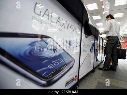 A customer tries out a Samsung Galaxy S III smartphone, released by Japan's largest mobile carrier NTT Docomo Inc, at an electronics store in Tokyo June 28, 2012. The Galaxy S III has received the most positive reviews among any of the Samsung smartphones, and the technology giant says the phone is on track to become its fastest selling smartphone, with sales likely to top 10 million in the first two months since its launch.   REUTERS/Yuriko Nakao (JAPAN - Tags: SCIENCE TECHNOLOGY BUSINESS TELECOMS)
