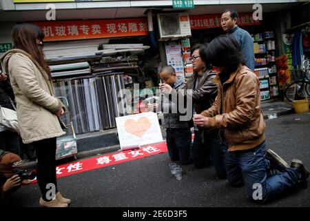 Three men kneel down holding cigarettes in front of a woman on a street during a performance in Shanghai February 14, 2012. Four artists and art students presented the performance as part of a demonstration calling for equality for men and women, local media reported. REUTERS/Aly Song (CHINA - Tags: SOCIETY) - Stock Photo