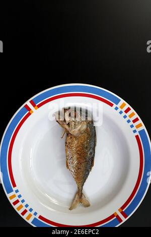 One of the fried mackerel is placed on a plate. On a black background. There is a blank space to place the text.