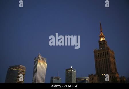 A view of the cityscape with the Palace of Culture and Science (R) and residential skyscraper Zlota 44 (2nd L), designed by architect Daniel Libeskind, is pictured during sunrise in Warsaw, Poland September 28, 2015. REUTERS/Kacper Pempel - Stock Photo