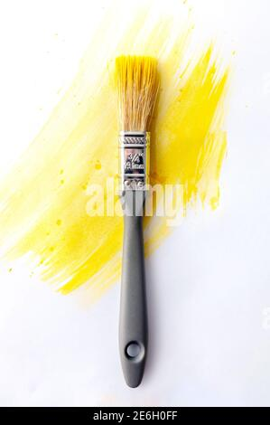 Color of the Year 2021. Gray Brush in Yellow Paint on White Background. Concept Repair.