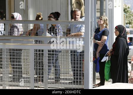 Syrians stand in line to enter the German embassy in Rabieh, Lebanon, September 18, 2015. Germany has become a magnet for thousands fleeing war and poverty in Asia, the Middle East and Africa. Many are escaping the civil war in Syria. REUTERS/Mohamed Azakir - Stock Photo