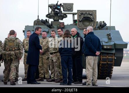 Britain's Prime Minister David Cameron (5th L) chats with soldiers from the Royal Welsh Infantry as they stand in front of a General Dynamics Ajax Specialist Vehicle (SV) Armoured Fighting Vehicle, at RAF Northolt in London, Britain November 23, 2015. Britain will invest an extra 12 billion pounds ($18 billion) in defense equipment over the next 10 years including nine Boeing submarine-hunting aircraft, Cameron said on Monday.   REUTERS/Justin Tallis/pool
