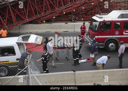 Paramedics attend to an injured passenger after she was trapped in a taxi after a bridge collapsed on the M1 highway near a busy offramp leading to Sandton, South Africa October 14, 2015. One person was killed and 17 were injured when a bridge collapsed over Johannesburg's main motorway on Wednesday, local emergency services said. The tangled wreckage of the metal, red-colored bridge was sprawled across Johannesburg's M1 highway near a busy offramp leading to the Sandton financial district where the stock exchange is located, snarling rush-hour traffic. REUTERS/Siphiwe Sibeko